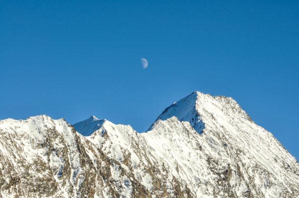 Verschneiter Berg mit Mond und blauen Himmel